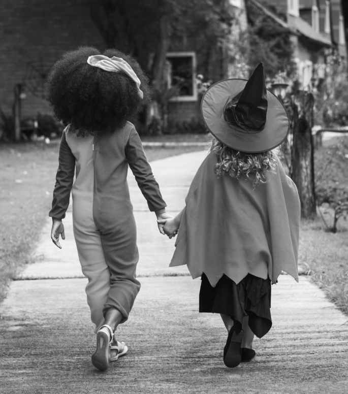 grayscale photography of two children holding hands together